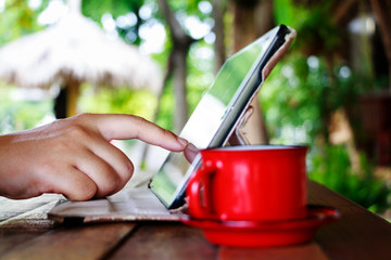 Finger touching on tablet with red cup on table in garden