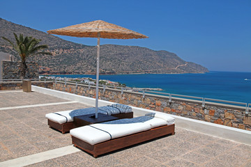 Sun beds and umbrellas on terrace in Greece