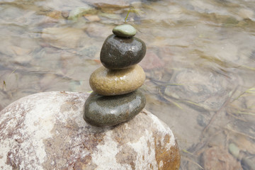 A stone cairn by a river.