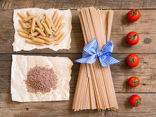 Pasta and  tomatoes on wooden background