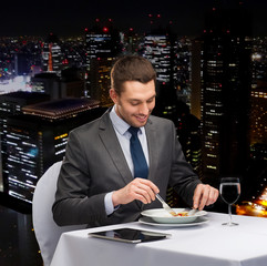 smiling man with tablet pc eating main course