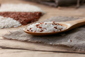 white and red rice in a wooden spoon