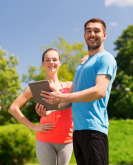smiling couple with tablet pc outdoors