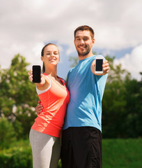 two smiling people with smartphones outdoors