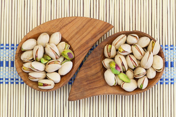 Pistachio nuts in miniature wooden bowls, close up