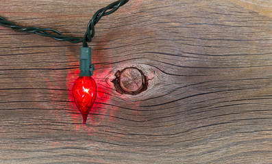 Red Christmas Light on Rustic Wood