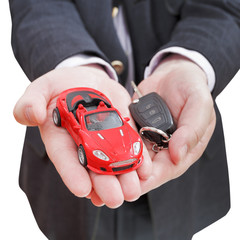 red car and key in seller's hand isolated