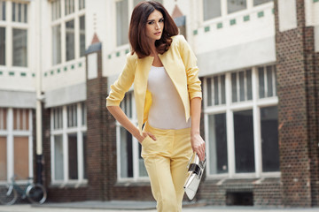 Smart brunette lady clothed yellow suit
