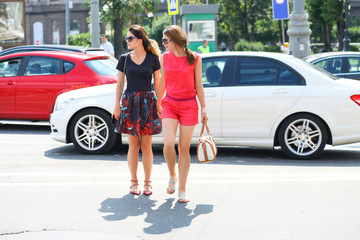 Two girlfriends crossing the road