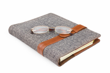 glasses on notebook on white background