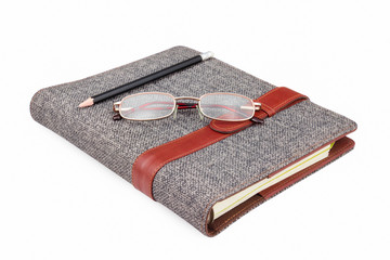 pencil, glasses on notebook on white background