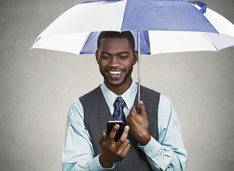 Happy executive reading news on smart phone, holding umbrella
