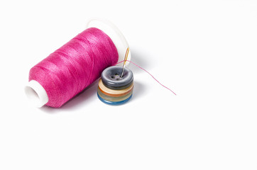Pink thread with needle and buttons