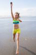 Happy child jumping with a sanddollar at the beach
