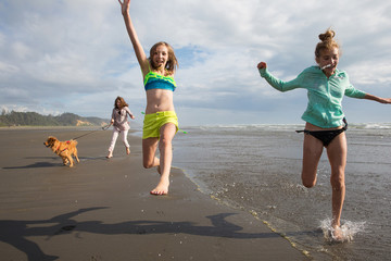 children running and jumping at the beach