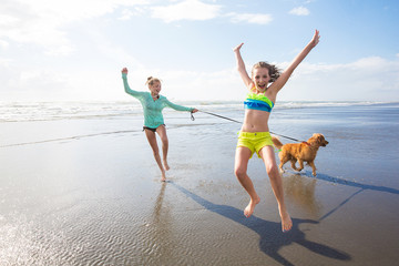 kids running, jumping and playing at the beach with their dog