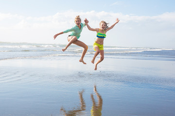 two kids jumping at the beach