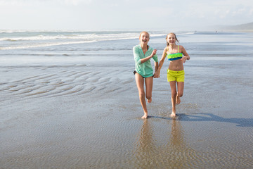 two kids walking and playing at the beach