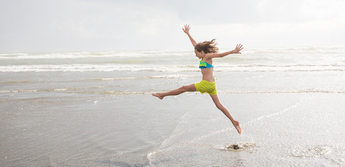child jumping at the beach