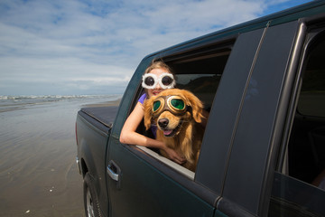 kid and dog driving with head out the window