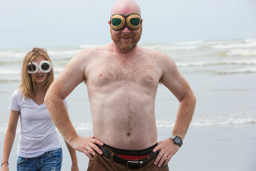 Shirtless bald man and daughter