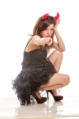 Chinese woman in black dress and devil horns squatting down poin