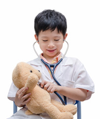 Young Asian doctor boy playing and curing bear toy isolated on w
