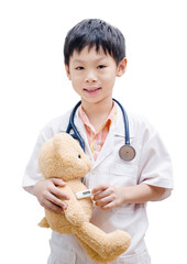 Asian doctor boy playing and measuring temperature bear toy isol