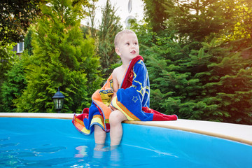 Cute child with towel on edge of swimming pool