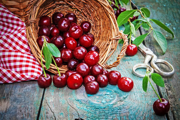 Ripe cherries in basket on old wooden table on countryside