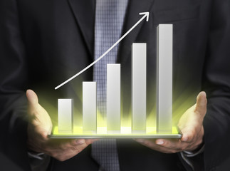 Businessman holding a graph showing growth