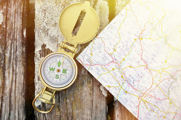 Compass and map on the wooden background