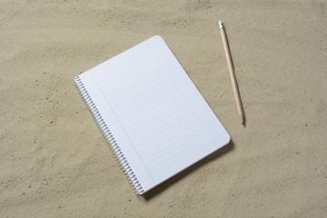 Cuaderno y lapicero en la arena