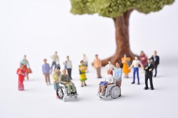 車椅子に乗っている高齢者と介助者のミニチュア人形