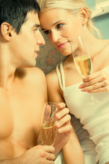 Couple with champagne at bedroom