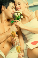 Couple celebrating with champagne at bedroom