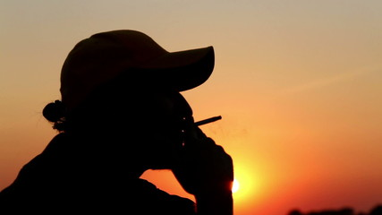 Portrait of a lonely man, smoking a cigarette at sunset.