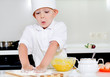 Little boy in chefs uniform baking in the kitchen