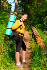 girl in the forest in the morning hike with a backpack