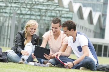 Three students look at an Ipad