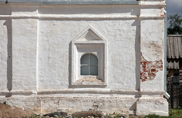 monastic cell window on old white wall