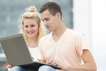 Two students watching at a laptop