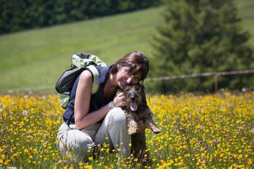 Donna e cane sul prato fiorito