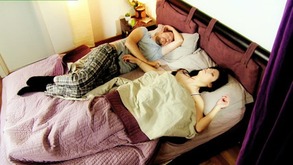 Couple in bed sleepin husband waking up wife