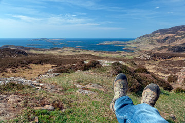 Man's legs relaxing after hiking on scottish islands