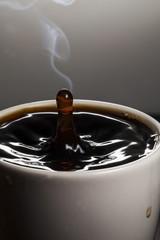Kaffeetropfen in Kaffeetasse fallend