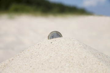 Coin in sand.