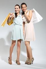 Dwie kobiety z papierowymi torbami na zakupy