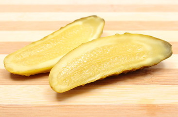 Marinated pickled cucumber lying on wooden cutting board