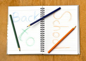 colorful pencil and notebook on wood background.The text back to